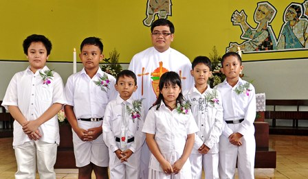 Children in Indonesia gather together after their First Communion in the Catholic Church.