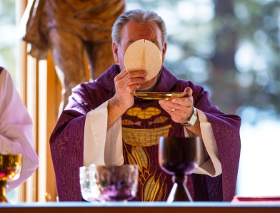 A priest, standing in the place of Jesus Christ during the one Perpetual Sacrifice of the Mass, consecrates ordinary bread and wine into the Body, Blood, Soul, and Divinity of Our Savior.