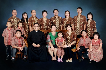 A Missionary of the Holy Family priest meets with his family in Indonesia with all wearing traditional outfits.