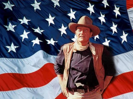 This is a classic image of John Wayne, in full Western uniform, standing in front of a giant flag of the United States of America.
