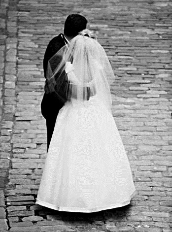 This is a classic black and white photograph of a groom and bride posing on a cobblestone road.