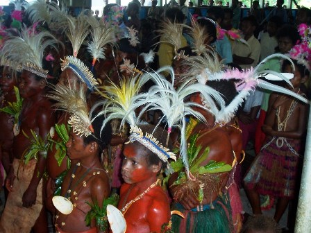 Children in a primitive area of Papua New Guinea dress in their cultural attire at a First Communion celebration.