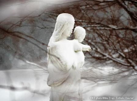 This is a picturesque winter scene of a snow covered statue of the Blessed Virgin Mary holding the Child Jesus.